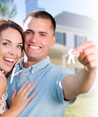 Photo of Happy couple holding keys with house in the background