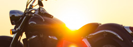 Photo of a motorcycle with the sun in the background