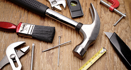 Image of home repair items including nails, a hammer, a wrench, a paintbrush, and a ruler